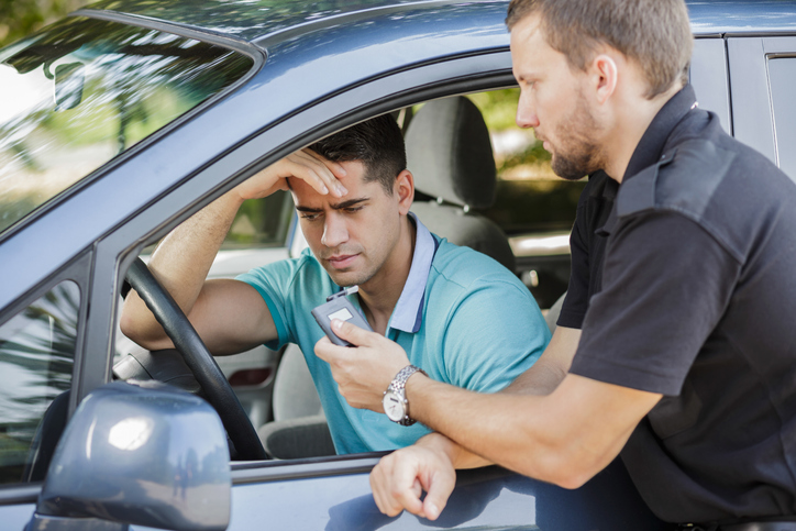 A driver considers taking a breathalyzer test.